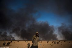 A sheperd tends to his blackened flock of sheep as oil wells, set ablaze by retreating Islamic State jihadists, burn in the background, in the town of Qayyarah, some 70 km south of Mosul, on November 20