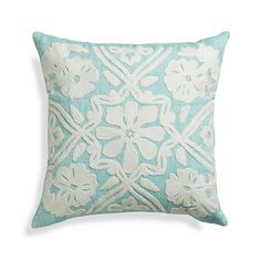 Classic floral motif relaxes soft and textural in white boucle yarns embroidered on linen chambray in pastel aqua. Skilled artisan hand guide machines to create the design, an exacting process. Pillow reverses to solid aqua.