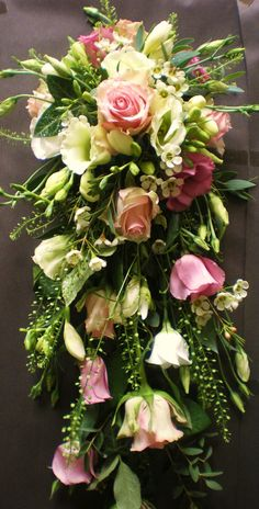 A shower bouquet is traditionally used to set the bride apart from the bridesmaids.  Why not choose the timelessly classic combination of roses, lisianthus and scented freesia to wow your guests as you make your entrance?