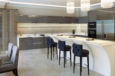 High gloss figured sycamore veneer kitchen. With mirror polished stainless steel trim detailing. White gloss curved island with curved Corian breakfast bar.