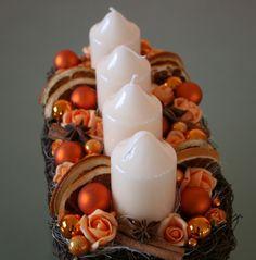 Velký adventní svícen meruňkovooranžový Velký adventní svícen v jemných meruňkových a oranžovýchodstínech, vproutěném košíkusjemně krémovými lakovanými svíčkami,zdobenýkvětyrůžiček,plátky pomeranče,skořicí,badyánem, hvězdičkamia skleněnýmikouličkami. Velikost svícnu - výška cca17cm, délka cca28 cm.