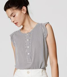 A little ruffle trim adds the perfect hint of sweet. Jewel neck. Sleeveless. Button henley placket. Ruffle trim at shoulders. Back yoke with shirred detail. Shirttail hem.