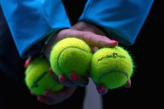 A ballkid displays Australian Open tennis balls in the fourth round match between Caroline Wozniacki of Denmark and Svetlana Kuznetsova of Russia during day eight of the 2013 Australian Open at Melbourne Park on January 21, 2013 in Melbourne, Australia.