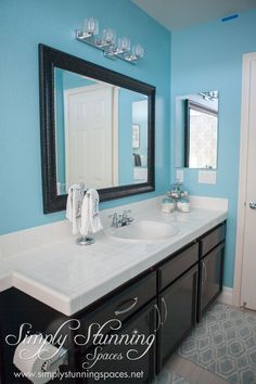 Simply Stunning Spaces bathroom design. Don't feel you need to stick to basic paint colors in the rooms of your home. Use your favorite color to inspire the walls in your bathroom! Bright walls in a smaller room such as a bathroom add positive energy and of course, look great! The combination of light floors contrasted perfectly with dark cabinetry and bright walls creates the perfect environment in this bright and clean bathroom.  http://simplystunningspaces.com/