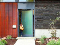 The 6-by-10-foot main entry door frames a panel of frosted glass with dark-gray aluminum. PHOTO BY Gibeon Photography