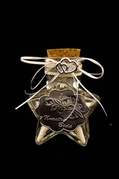 Wedding party favors made of a glass container in the shape of a star with a silver plaque in the front with the occasion on it. The container is used to hold grains of rice.
