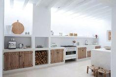 Cucina in muratura rustica, con accenti moderni: sportelli in legno grezzo, piccolo camino aperto - pavimenti in travertino e soffitto con travi in legno dipinte in bianco per un ambiente molto luminoso
