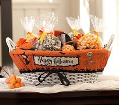 """Halloween Treat Basket & Liner  Colorful, spooky and festive, our goodies basket creates a welcome spot for trick-or-treaters or a delightful centerpiece for a fun Halloween event. Liner adds a decorative touch to our treat basket and is made of cotton canvas with our exclusive Halloween illustrations.  Liner reads """"Happy Halloween"""" on one side; the other side is left blank for personalization."""