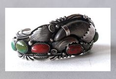 This is an extremely ornate, well designed and constructed bracelet. It has a beautiful balance of color, shape, style and size. The manner in which the elements have been place in respect to each other is perfect. Coral is just enough color to accent the cool tones of the silver and turquoise, and the bear claw is a component not often seen in such bracelets, but adds dimension to the piece. There are arrow-like markings on the back on either side of the sterling. This may be a hallmark…