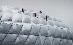 Climbers clear snow from the roof of the stadium of FC Bayern Munich in Munich