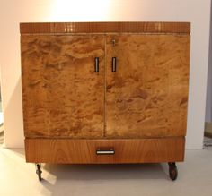 Art Deco drinks trolley in figured walnut with original wheels and bakelite and metal handles. Lid lifts to a compartmented drinks cabinet with lower drawer. H 70.5cm, W 70.5cm, D 42.5cm. French, ca. 1930 (hva)