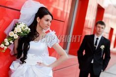 bride and groom by the red wall
