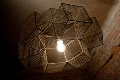 This is S/M style chandelier - raw, symmetric and as plain as possible. It gives web-like shadows on ceiling.  It's made with 9 test-tube baskets bought from Polish Army. I skew some of them and connect all of them with wire