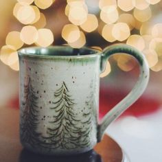 Handmade pottery mug with etched pine tree design in green and white. Sipping a hot drink by the Christmas lights. Cozy winter holiday scene.