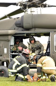 "An Oregon National Guard crew chief from Charlie Co., 7-158 Aviation, directs first responders, as they load a mock injured ""patient"" onto an HH-60 Blackhawk MEDEVAC helicopter during the Vigilant Guard Exercise"
