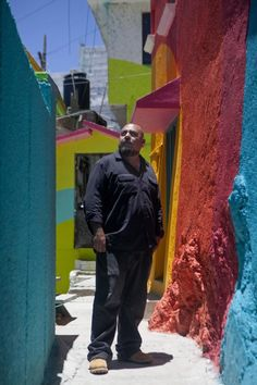 Enrique Gomez, who goes by the name of MYBE: Artists Transform Neighbourhood Into One Giant, Mind-Blowing Mural. Photo by Sofia Jaramillo/APMexican