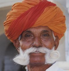 The proud face of a Rajput, with traditional headgear.