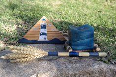 Cozy Lighthouse é uma decoração da ArteNatis constituída por:  - Uma peça triangular em madeira de carvalho, com acabamento de verniz mate, e realizada com uma pintura realizada à mão de um farol;  - Um ramo de centeio;  - Uma vela decorativa azul, colocada em cima de quatro peças cilíndricas em madeira natural.