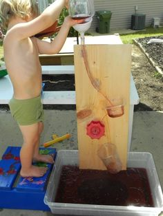 Cheap water maze DIY - funnel, plastic tubing, tupperwear, water wheel off a sand toy, plastic cup.