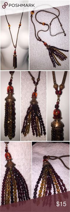 """Amber Ruby Topaz Aurora Borealis tassel necklace Vintage Faceted Amber Topaz Ruby Aurora Borealis beaded tassel necklace. Necklace is combined with Amber beads, Topaz aurora borealis beads, ruby red beads, & antique copper metal beads. The tassel end has 10 strands of various shape & size dangling beads that come together on a antique copper metal dome cap that is adorned with ruby red stones around it. The metal snake chain is also antique copper in tone. Measurements: Length is 29""""…"""
