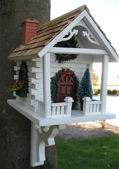 Christmas Cabin.  Wreaths, Garland and miniature Poinsettia flower boxes decorate this style that will be sure to delight the birding enthusiast with the Holiday Spirit. Entrance hold measures 1 1/4 inch to accommodate common cavity dwellers such as Wrens, Finches, Chickadees, Nuthatches and Titmice. #Christmas #cabin #birdhouse #birdhouses
