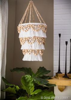 Get the coastal boho look that has you feeling like everyday is a beach day! To DIY: 1) Attach three embroidery hoops together using waxed thread on the inside of the embroidery hoops. 2) Tie wax thread all around top tier to hang chandelier. 3) Attach white tassel fringe to all 3 tiers using hot glue. TIP: Hang while gluing on fringe. 4) Attach beads to each tier using wax thread. TIP: Use an odd number of beads. 5) Mix and match beads for an interesting look.