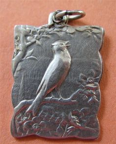 """Antique German Silver Perched Robin Bird Slider Locket Pendant Charm Stunning   eBay    Exquisite antique, circa 1900s, perched robin slider locket pendant or charm. In excellent antique condition with beautiful detail.    Locket Size: 15/16"""" by 3/4""""   Weight: 4.1 gr   Material: 800 Silver   Hallmarks: DEP 800. DEP is short for depose which is French for registered/protected design. 'DEPOSE' wasn't used on German silver after 1914 because of the start of the 1st World War with France."""
