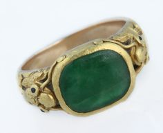 An unusual Chinese jadeite and gold ring, circa 1850,  the cushion shaped apple green Jadeite ring with stylised mythical beast cast and carved shank