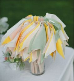 Pastel pennants are gathered in a vase at a reception, ready for guests to wave during the bride and groom's send-off. #Weddings