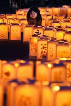 Menina se senta entre lanternas de papel durante evento em Natori para homenagear as vítimas da tragédia de março de 2011 no Japão. Foto: Kyodo - 11.mar.2015/Reuters
