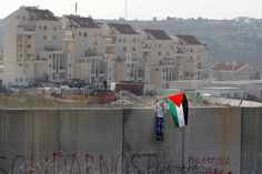 A Palestinian protester places a flag on the controversial Israeli barrier in the West Bank village of Bilin during clashes with Israeli security officers after a rally marking the 48th anniversary of the founding of the Fatah movement.    Photo: Ammar Awad/Reuters  csmonitor.com