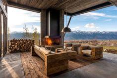 modernes haus überdachte terrasse vorne außenkamin holz möbel