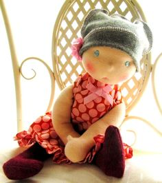 One of my earlier dolls. I love this style. Long crimson wool felt boots, crazy polka dot ruffle dress, gray hat, and a flower, sitting on my chair. <3