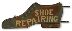 """American, probably early 20th century, in the form of a man's dress shoe, hollow construction of sheet steel, having iron hanging supports. A two-sided sign, both sides painted similarly in colors of red, yellow, green and black with SHOE REPAIRING in white lettering, 24"""" high x 64"""" long x 4"""" deep."""