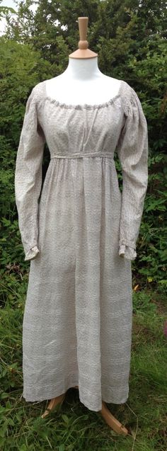 c1815 fall-front gown. Self stripe with geometric lilac print. Fairly low waist. Belt and cuff ties have piped edges. Fastens at front with pins.