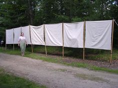Constructing a fabric wall to surround an encampment.