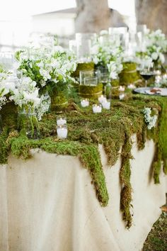 Totally over-the top, but I love the natural moss over the natural-fiber table linens, and the moss-wrapped candle jars. So, you know, if I find myself with a lot of money to spend on a wedding someday.... (this will not happen)