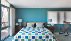Benjamin Moore's Teal Ocean is a calming hue on the master bedroom walls. A pair of Lucite lamps with pale blue silk shades from Filament top the vintage bedside tables.