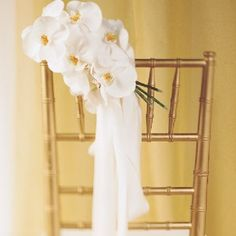 Delicate butterfly orchids are clustered in a hand tied bouquet and fastened to the back of this chair.