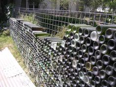 bottle wall by putting bottles in a mesh fencing bottle crafts wall Imagine That. Wine Bottle Garden, Wine Bottle Wall, Bottle House, Bottle Art, Bottle Crafts, Gabion Wall, Bottle Trees, Recycled Bottles, Recycled Glass