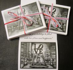 "LOVE Sculpture (Philadelphia) Christmas Cards; Pack of 10 cards (with envelopes) for $9.00. Hand-drawn (by me!) in black ink, printed on 4.25"" x 5.5"" white card stock, package bound with ribbon. Shows Robert Indiana's LOVE sculpture in Philadelphia with mistletoe hung between the lower letters and a couple standing below. Lamp posts and barriers decorated for the holidays. Holiday message inside."