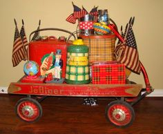 Vintage wooden wagon all packed up read for 4th of July parade with vintage plaid thermoses, picnic tins, 1940's cooler and lots flags