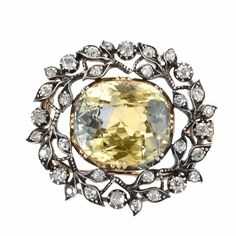 Antique Silver, Gold, Bicolored Sapphire and Diamond Brooch. One cushion-shaped yellow sapphire ap. 26.50 cts., 32 old-mine cut diamonds ap. 1.45 cts., brooch fitting detachable, ap. 12.4 dwts. With GIA report no. 51400578, no indications of heating.