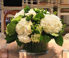 A lush, classic arrangement of white hydrangeas, white roses and hypernicum berries.