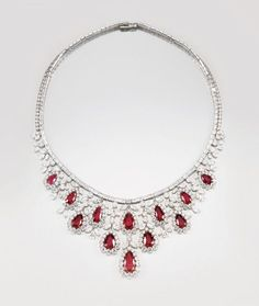 A Magnificent Unheated Burmese Ruby and Diamond Necklace    The front designed as cascading fringes composed of twelve pear-shaped rubies, each framed by brilliant-cut diamonds, to a cluster surmount set with marquise-shaped and brilliant-cut diamonds, completed by a stright line articulated chain set with baguette and brilliant-cut diamonds, mounted in platinum, length approximately 42 cm. Necklace signed 'HW' with a Harry Winston