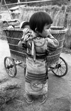 人形を背に子守りする少女、1956年。