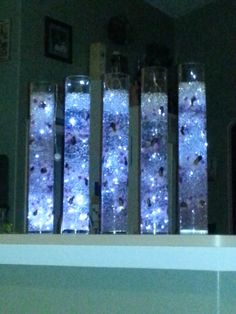 Tall cylinder vases with gel beads, fairy lights, and silk orchid heads