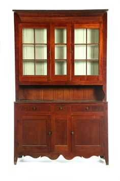 American early 19th century Step-back Cupboard, high cutout feet and scrolled apron, paneled doors flanking stationary panel with three dovetailed drawers in base.  Top has high pie shelf with S-scroll ends, double doors each with panes of old glass and a stationary panel with three panes.  Wide cove molded cornice, 98.5 H. x 60.5 W. x 16.75 D.