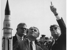 President John F. Kennedy, right, gets an explanation of the Saturn V launch system from Dr. Wernher von Braun, center, at Cape Canaveral in November 1963. NASA Deputy Administrator Robert Seamans is to the left of von Braun.