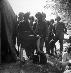 A French dancer (of the first USO show in Normandy) speaking to some US soldiers at the dressing tent. 29th Infantry Division